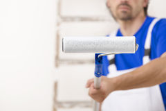 Painter man aiming at you with paint roller. Stock Images