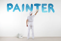 Painter man with paint brush drawing a blue painter text. Isolated on the blank white wall Stock Photos