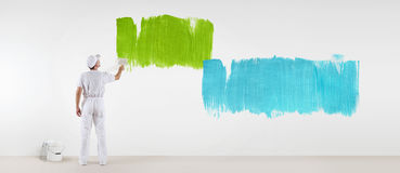 Painter man with paint brush painting colors samples, isolated. On blank white wall background, web banner stock image