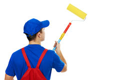 Painter man in uniform with paint roller Royalty Free Stock Photos