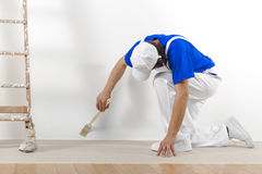 Painter man at work with brush. Painting a white wall Royalty Free Stock Photos