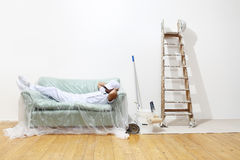 Painter man at work, finished working and lies down on the couch Stock Image