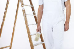 Painter man at work with a paint brush and ladder Stock Photos