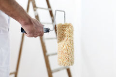 Painter man at work with a paint roller and ladder Royalty Free Stock Image