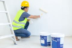 Painter man at work with a paint roller on the wall stock image