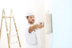 Painter man at work with a paint roller, wall painting Stock Photos