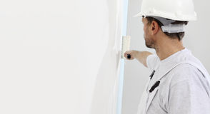 Painter man at work with a paint roller, wall painting. Concept royalty free stock photography