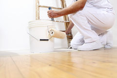 Painter man at work with a roller, bucket and scale, bottom view Royalty Free Stock Photos