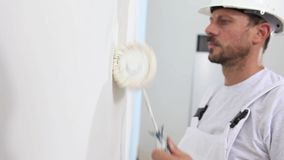 Painter man at work, with roller painting wall, painter house stock footage