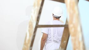Painter man at work, with roller painting wall, wooden ladder in close up stock footage