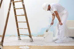 Painter man at work takes the color with paint brush from the bu Royalty Free Stock Photo