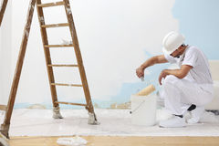Painter man at work takes the color with paint roller from the b. Ucket on the floor royalty free stock photo