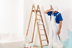 Painter man at work. Takes the color with paint roller from the bucket. With copy space stock photo