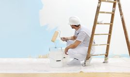 Painter man at work takes the color with paint roller from the bucket and look the wall, copy space template. Painter man at work takes the color with paint royalty free stock photo