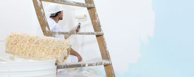 Painter man at work, with wooden ladder and blank wall for copy space, web banner. Template stock photography