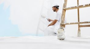 Painter man at work, with wooden ladder and blank wall for copy space, web banner. Template stock image
