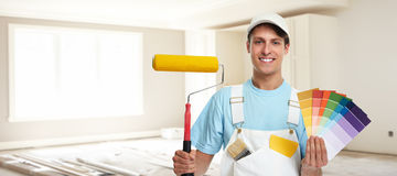 Painter man. Young painter man with painting roller. House renovation background Royalty Free Stock Photos
