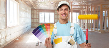 Painter man. Young painter man with painting roller. House renovation background Royalty Free Stock Photo