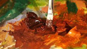 Painter mix two brown and orange colors oil. Painting on palette with other different and colored paints like green brown, yellow, close up, slow motion stock video footage