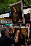 Painter in Montmartre, Paris. PARIS, JULY 28: A bohemian look painter is painting a series of portraits about old mens in Tertre square of Montmartre, where lot Royalty Free Stock Photography