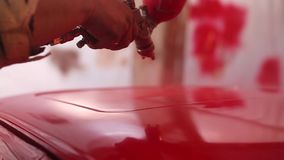 Painter paint the red car in garage stock video footage
