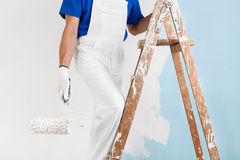 Painter with paint roller on ladder. Closeup headless portrait of painter with gloves and paint roller climbing up a wooden vintage ladder to paint a wall Royalty Free Stock Photos