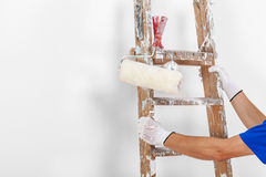 Painter with paint rollers and wooden ladder Stock Photography