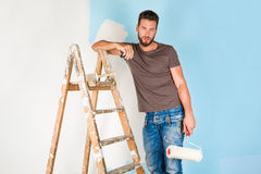Painter in paint splattered shirt painting a wall royalty free stock image