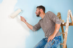 Painter in paint splattered shirt painting a wall Stock Photo