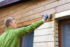 Painter with paintbrush painting house wooden facade Stock Image