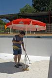 Painter painting the bottom of a swimming pool Stock Photo