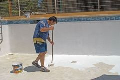 Painter painting the bottom of a swimming pool Royalty Free Stock Photo