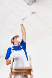 Painter painting ceiling with brush Stock Image