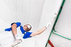 Painter painting ceiling with brush Royalty Free Stock Images