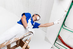 Painter painting ceiling with brush Royalty Free Stock Image