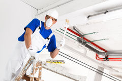Painter painting ceiling with brush Stock Photo