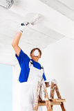Painter painting ceiling with paint roller Stock Photo