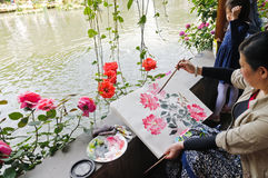 A painter painting Chinese rose seriously in the garden Royalty Free Stock Images