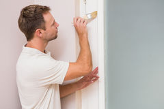 Painter painting the door white. In a new house Royalty Free Stock Images