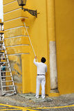 Painter painting the facade of a ancient buildind with roller, Spain Stock Photo