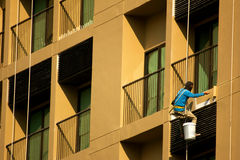 Painter painting on high rise building Stock Photography