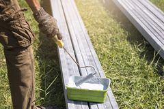 Painter painting metal. worker holding   roller and dipping into. Paint bucket in park Stock Image