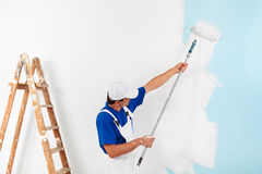 Painter painting with paint roller. Painter with cap painting a wall with paint roller and wooden vintage ladder, with copy space Royalty Free Stock Photo