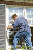 Painter painting trim around doors & windows Stock Photo