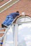 Painter painting trim around doors windows Royalty Free Stock Images