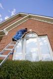 Painter painting trim around doors windows stock images