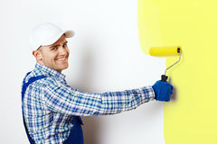 Painter painting a wall. Happy young male painter painting a wall royalty free stock image