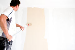 Painter painting wall at home. A painter painting a wall in renovated home. Focus on the roller brush Stock Photo