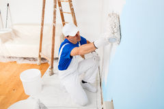 Painter painting a wall with paint roller. Above view of painter with cap and gloves painting a wall with paint roller, wooden vintage ladder and bucket on Royalty Free Stock Photography