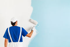 Painter painting a wall with paint roller. Back view of  painter in white dungarees, blue t-shirt, cap and gloves painting a wall with paint roller, with copy Stock Photo